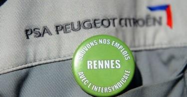 un-employe-de-l-usine-psa-de-la-janais-pres-de-rennes-porte-un-badge-symbole-de-lutte-pour-la-preservation-des-emplois-le-28-aout-2012