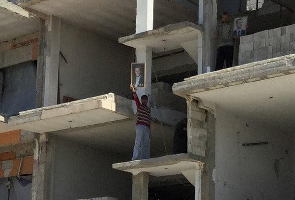 A Homs, sur les lieux de l'attentat , un ouvrier brandit un portrait de Bachar el-Assad