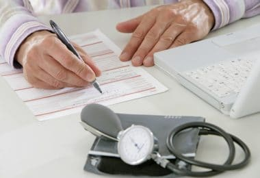 Médecin rempliçant une feuille maladie